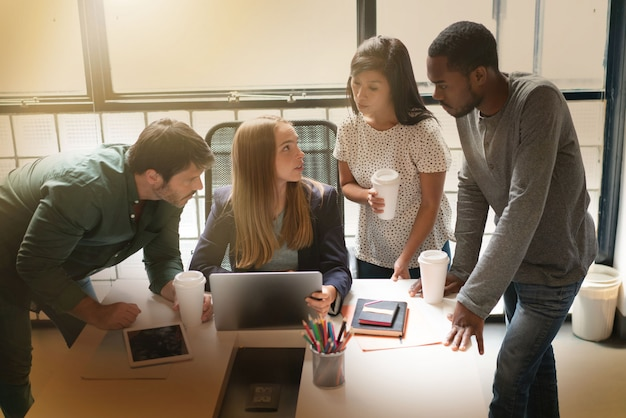 Co workers being shown latest presentation by young attractive woman