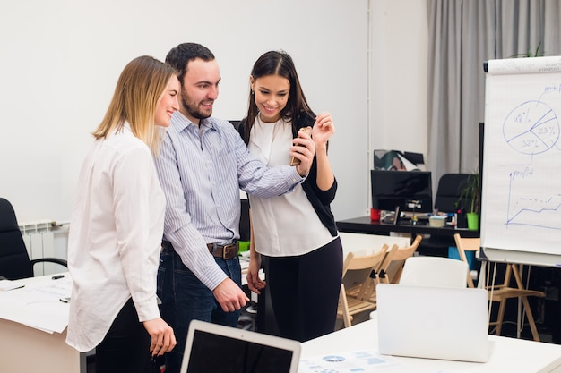Co-workers taking self portrait and making funny gestures with hands at small office