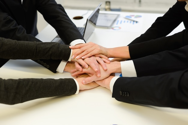 Co-workers with hands together