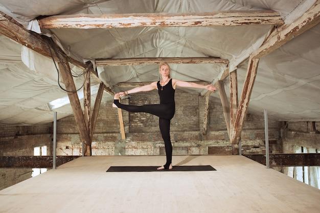 コーチ。若いアスリート女性は、放棄された建設ビルでヨガを練習します。心身の健康バランス。健康的なライフスタイル、スポーツ、活動、減量、集中の概念。