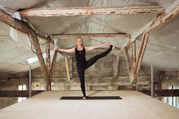 코치. 젊은 체육 여자 버려진 된 건설 건물에 요가 연습. 정신적 및 신체적 건강 균형. 건강한 라이프 스타일, 스포츠, 활동, 체중 감소, 집중력의 개념.