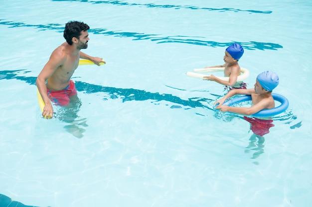 레저 센터의 수영장에서 상호 작용하는 코치와 학생들