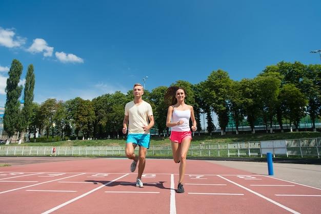 운동하는 코치와 트레이너. 경기장 트랙에서 실행 하는 커플. 푸른 하늘에 남자와 여자 화창한 야외입니다. 경쟁과 미래의 성공에 주자. 스포츠 및 건강 피트니스.