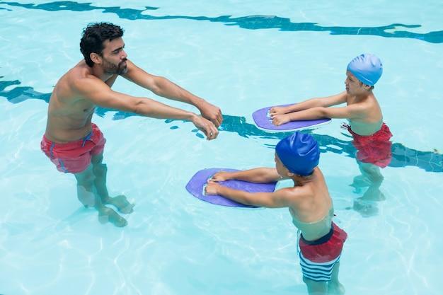 레저 센터의 수영장에서 어린이 수영을 돕는 코치