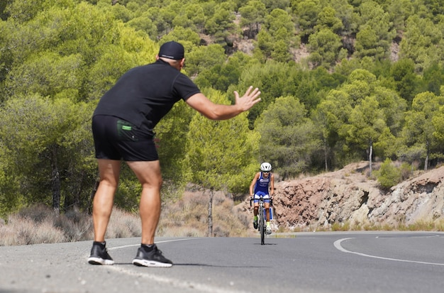 Coach and father cheering up his student and son in a cycling race