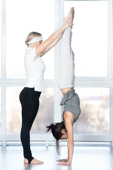 Coach helping student to do handstand