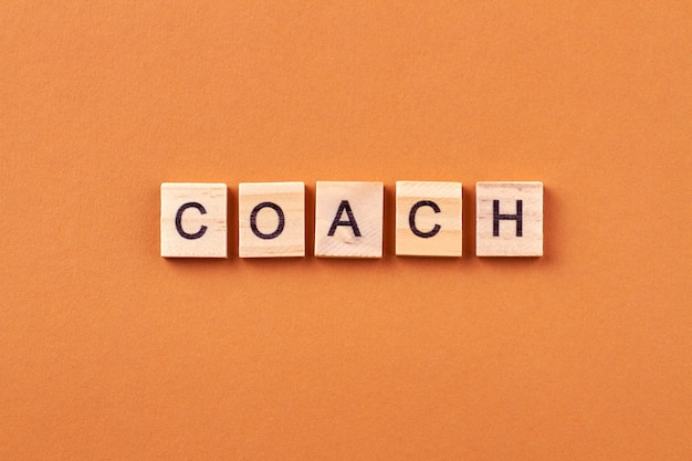 Коуч - это специалист, который занимается наставничеством. вдохновение и мотивация для бизнеса. письма на деревянных кубиках, изолированные на оранжевом фоне.