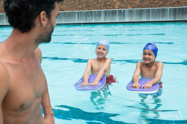 레저 센터에서 수영장에서 노는 학생들을 바라 보는 코치