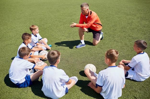 주니어 풋볼 팀과 대화하는 코치