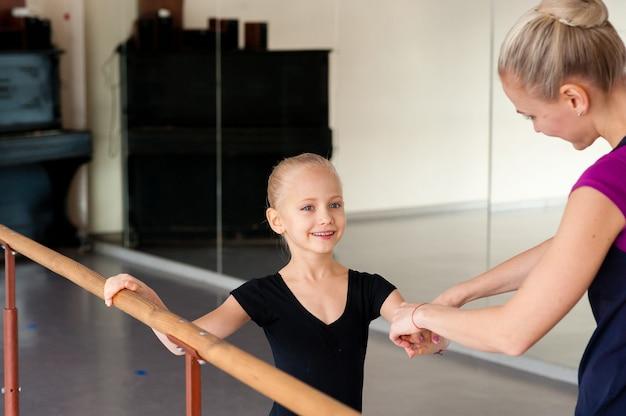 Тренер учит девушку балету
