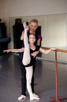 The coach teaches the girl how to stretch the choreography