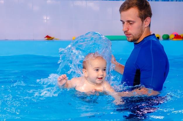 Тренер учит малыша плавать в бассейне