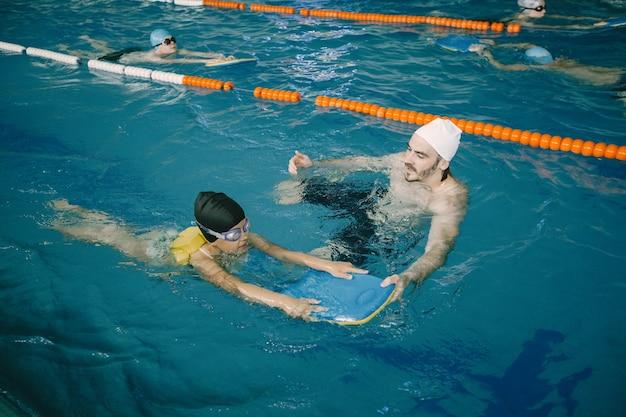 屋内プールで子供に泳ぎ方やダイビングの仕方を教えるコーチ。水泳レッスン、子どもの発達。