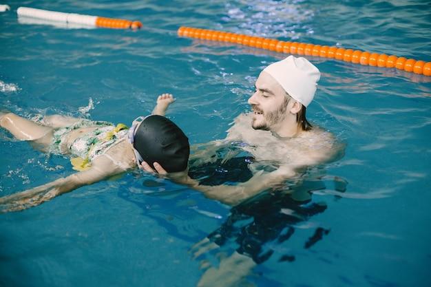 실내 수영장에서 아이에게 수영과 다이빙을 가르치는 코치. 수영 강습, 어린이 발달.