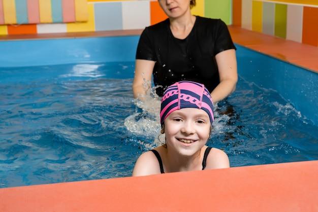 Тренер учит ребенка в крытом бассейне плавать и нырять