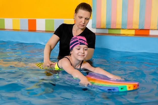 Тренер учит ребенка в крытом бассейне плавать с флаттер-доской
