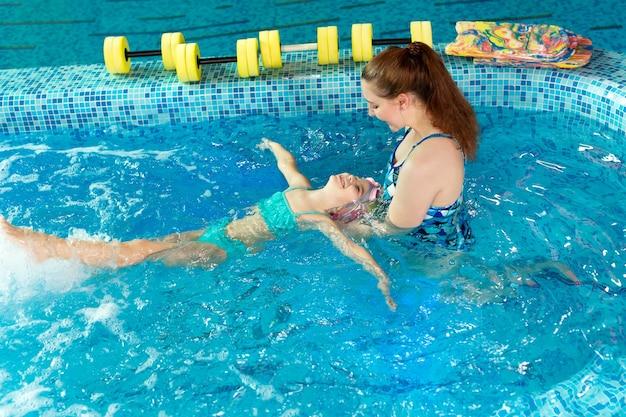 실내 수영장에서 아이에게 수영하는 방법을 가르치는 코치