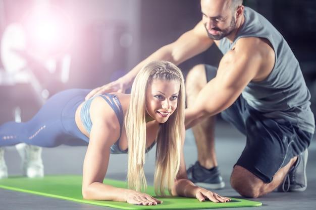 Тренер и спортсменка делают планку в тренажерном зале.