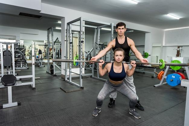 ジムで若くて美しい女性を訓練するコーチ
