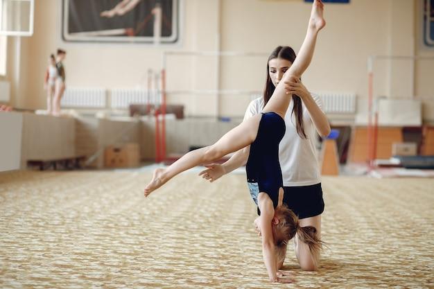 Тренер со студентом. девушки-гимнастки, выполняют различные гимнастические упражнения и прыжки. дети и спорт, здоровый образ жизни.
