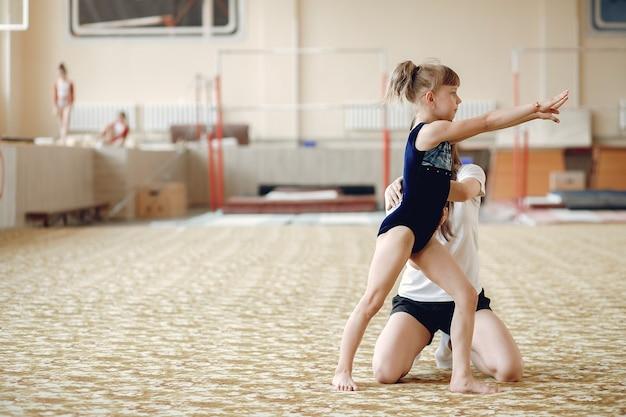 학생과 함께 코치하십시오. 여자 체조 선수는 다양한 체조 운동과 점프를 수행합니다. 자녀와 스포츠, 건강한 라이프 스타일.