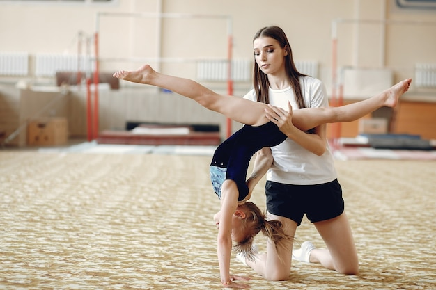 Coach with student. girls gymnasts, performs various gymnastic exercises and jumping. childs and sport, a healthy lifestyle.