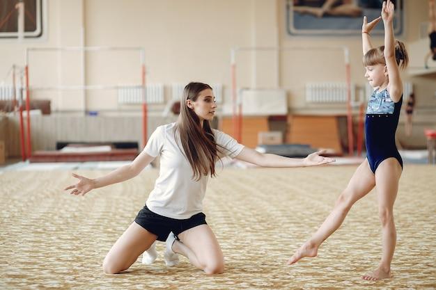 Allenatore con lo studente. ragazze ginnaste, esegue vari esercizi ginnici e salti. bambini e sport, uno stile di vita sano.