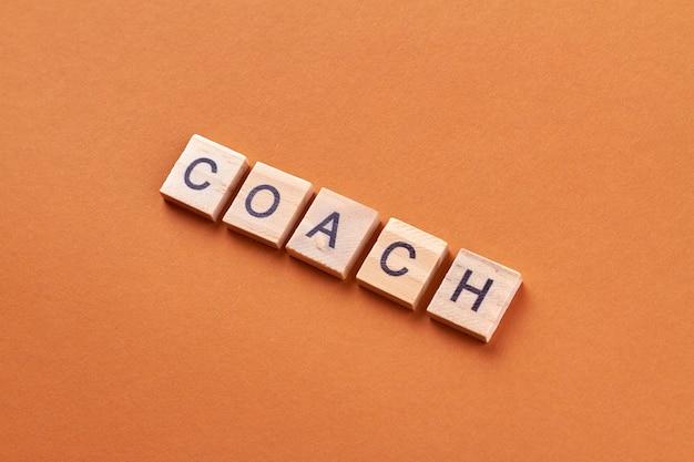 Слово тренера на деревянных блоках. деревянные блоки с буквами, изолированные на оранжевом фоне.