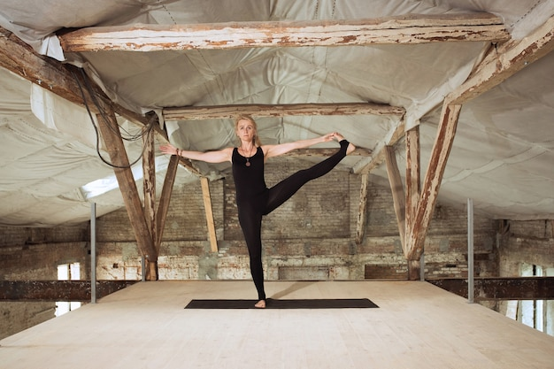 Allenatore. una giovane donna atletica esercita lo yoga su un edificio abbandonato. equilibrio della salute mentale e fisica. concetto di stile di vita sano, sport, attività, perdita di peso, concentrazione.