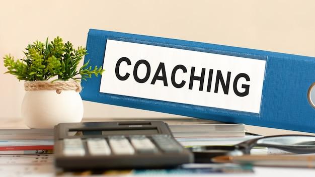 Коучинг - синяя папка на столе в офисе с калькулятором, ручкой и зеленым горшечным растением. может использоваться для бизнеса, финансов, образования, аудита и налоговой концепции. выборочный фокус.