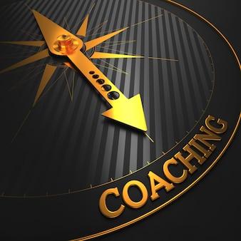 コーチング。 「コーチング」という言葉を指す黒いフィールド上の黄金のコンパス針。 3dレンダリング。