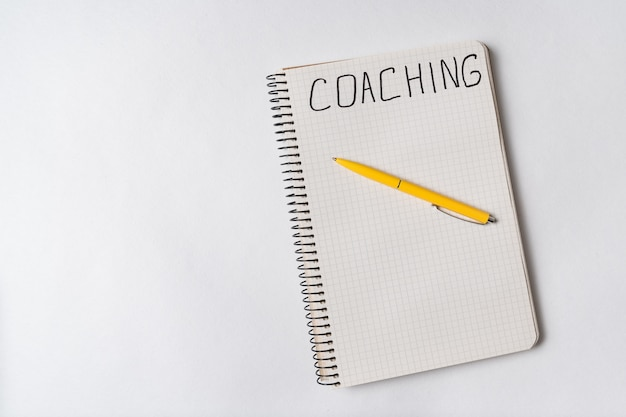 Coaching, word written on notebook, white background. top view of notepad and pen. copy space