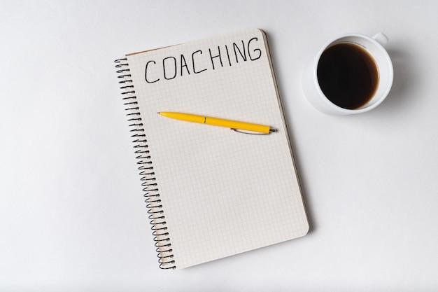 コーチング、ノートに書かれた言葉。メモ帳、ペン、一杯のコーヒーの平面図です。