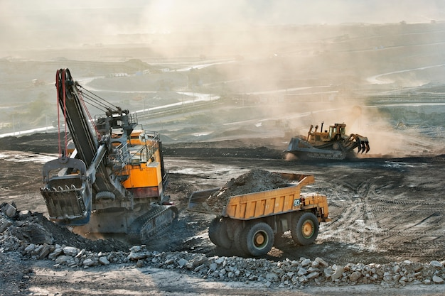 Coal mine area many heavy truck and excavator machine for mining industry