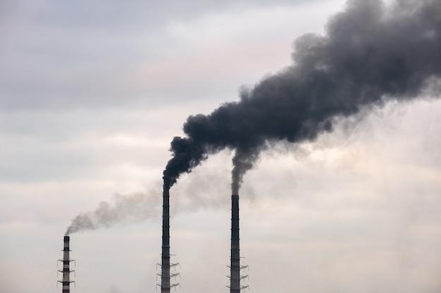 Высокие трубы угольной электростанции с движением черного дыма вверх в загрязняющую атмосферу.