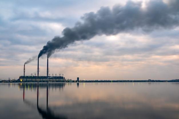 黒い煙が上向きに移動する石炭火力発電所の高いパイプが反射で大気を汚染している