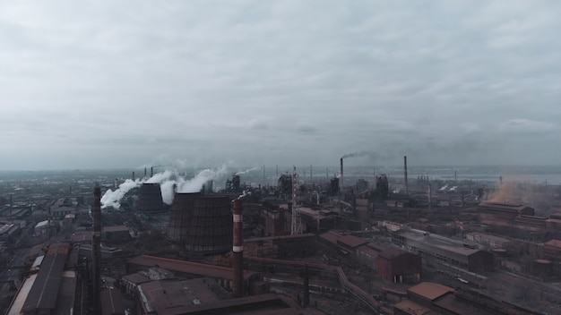 Coal power plant high pipes with green poison smoke moving up polluting atmosphere of the city