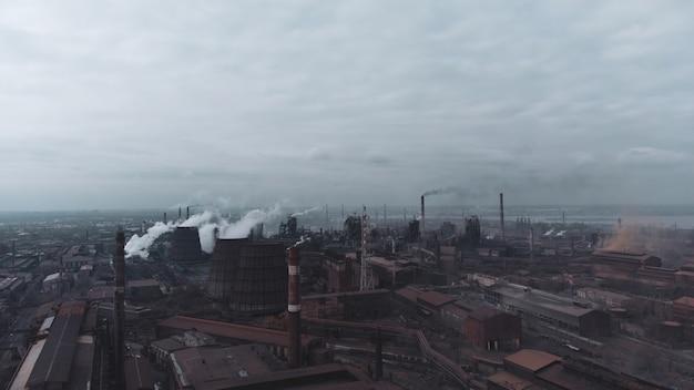 石炭火力発電所の高いパイプと緑の毒煙が街の汚染された雰囲気を上っていく