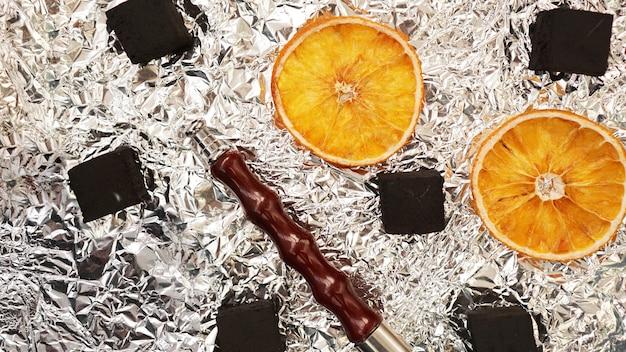 마른 오렌지와 물담배 파이프가 있는 호일 배경의 물담배용 석탄 - 위쪽