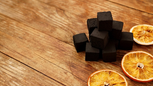 Coals for hookah on wooden background with dry oranges. place for text