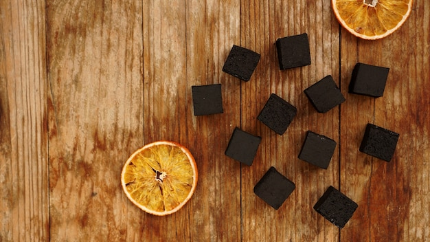 Coals for hookah on wooden background with dry oranges - top view