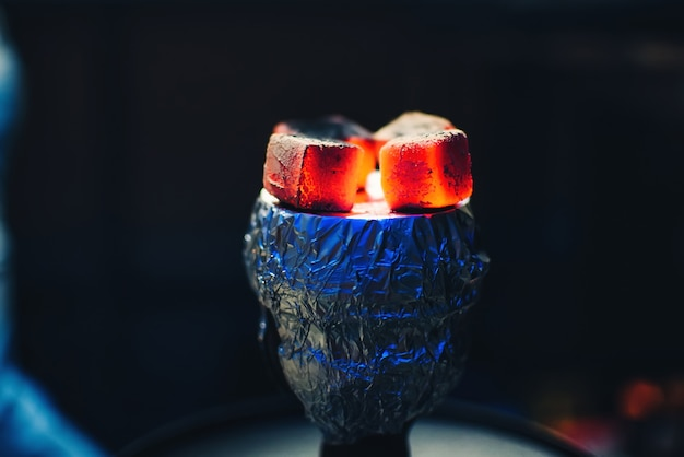 Coals of shisha on foil on bowl with tobacco smoking and red hot