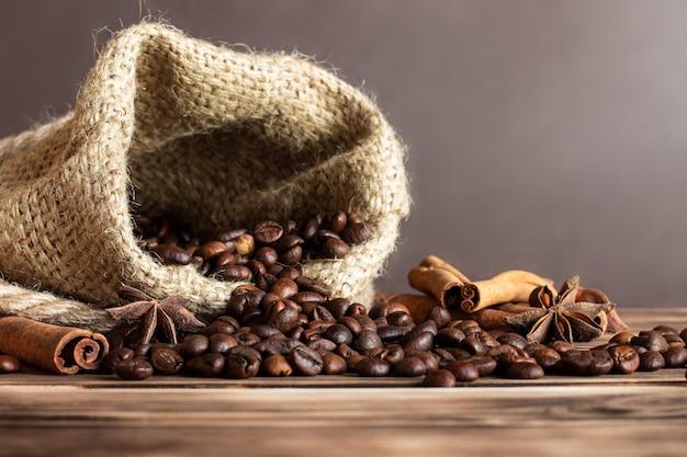 계피 스틱과 아니스 별이 달린 불에 탄 나무 탁상에 커피 알갱이를 뿌린 거친 삼베 자루.