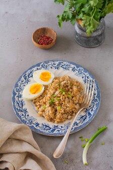 卵と玉ねぎが入った粗いオートミールのお粥。心のこもった健康的な朝食またはランチのコンセプト。セレクティブフォーカス。