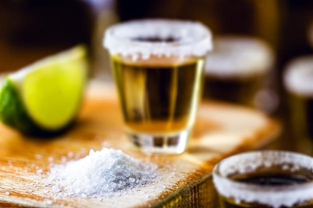 底の粗い塩、スポットフォーカス。メキシコからの典型的なメキシコの飲み物であるテキーラの消費のための成分。