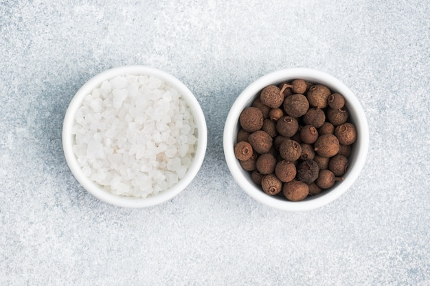 Coarse salt and black peppercorns in white ceramic bowls on gray concrete, copy space top view.