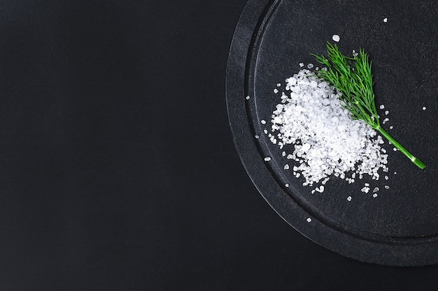 黒いテーブルの上の粗い塩の結晶