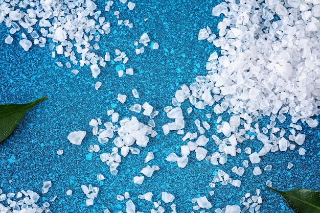 塩辛い広告のための青いテーブル海塩の背景に粗い塩の結晶