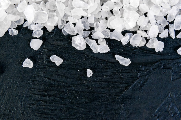 Coarse sea salt on black slate stone background, closeup