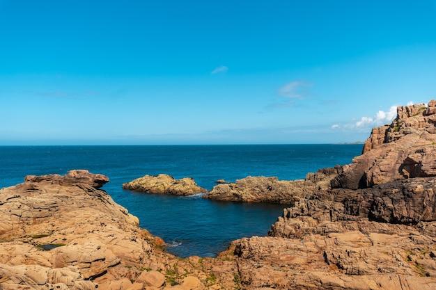 フランス、ブルターニュのコートダモール、ペロスギレックの町にあるプルマナッコ港の灯台ミーンルス沿いの海岸。